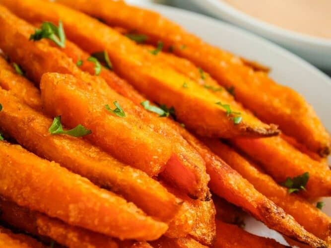 Air Fryer Sweet Potato Fries on white plate with bowl of sriracha mayo in background