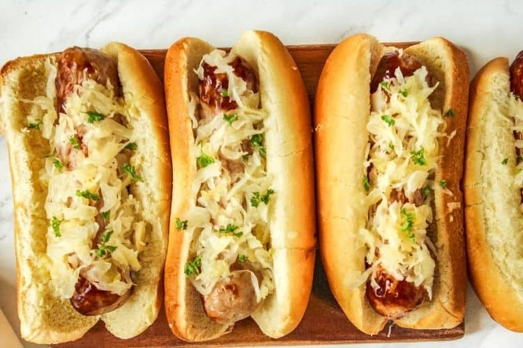 Air Fryer Bratwurst in a row in buns with sauerkraut on top