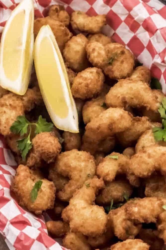 Air Fryer Popcorn Shrimp in a red basket with lemon wedges