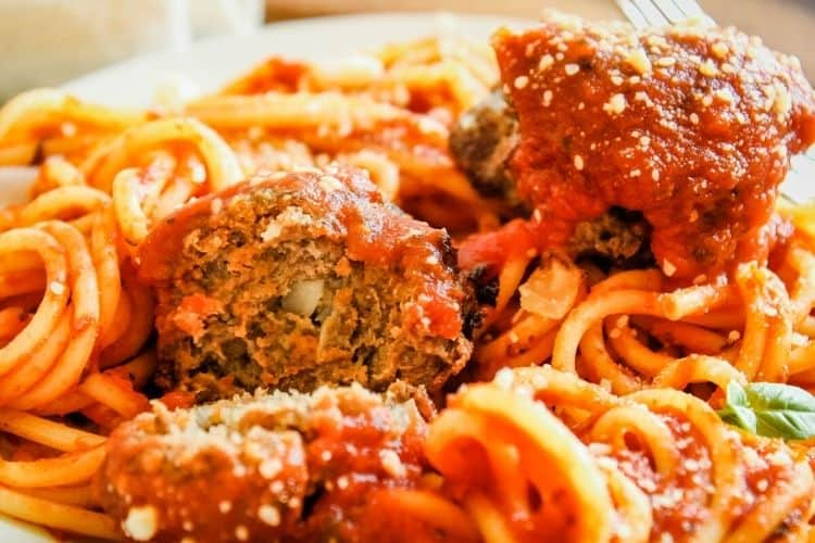 Spaghetti and meatballs covered in sauce with meatball broken open