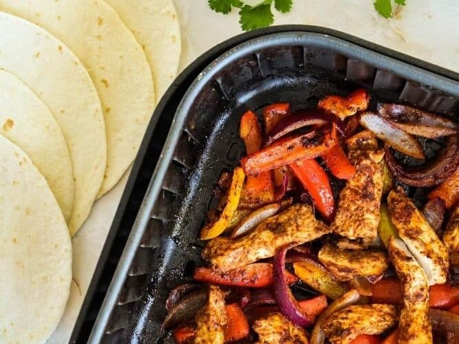 Cooked chicken fajitas inside air fryer with tortillas and lime wedges next to it