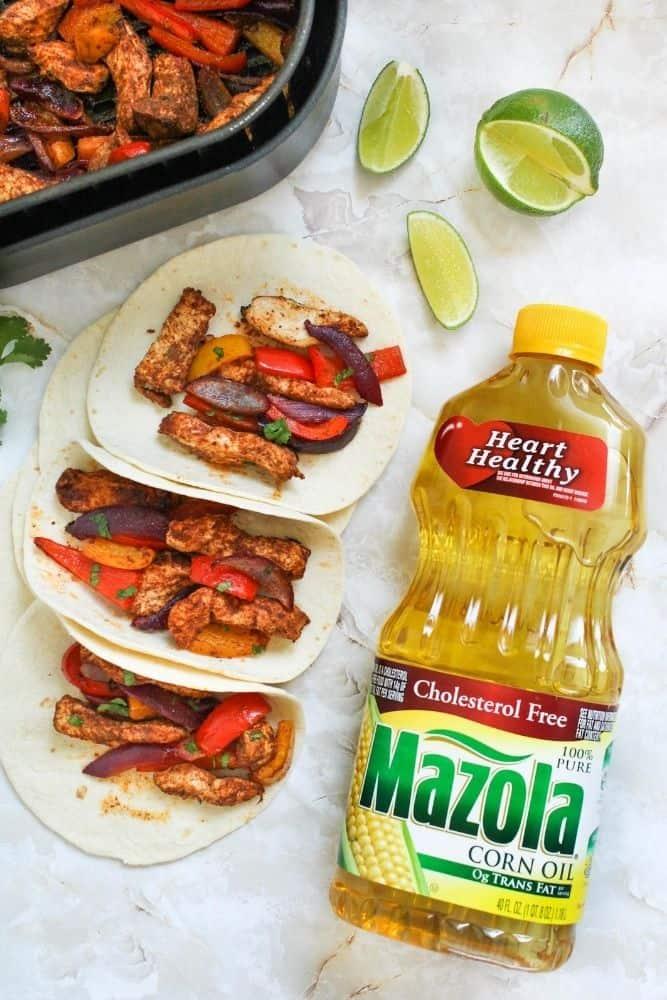 Air Fryer Chicken Fajitas inside tortillas with Mazola Corn Oil bottle next to it