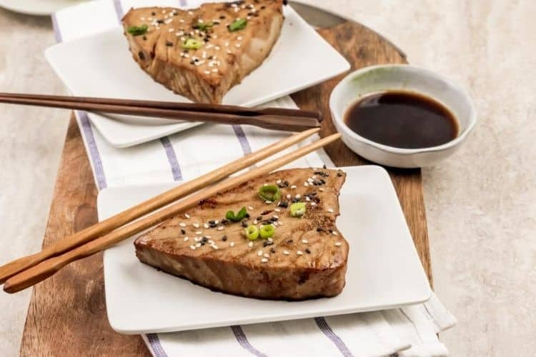 Cooked whole tuna steak on white plate with chopsticks and sauce