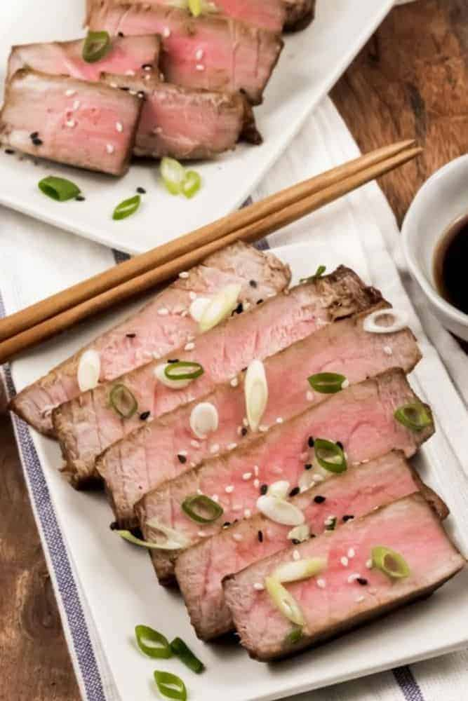 Air Fryer Tuna Steaks sliced on a rectangular plate with chopsticks