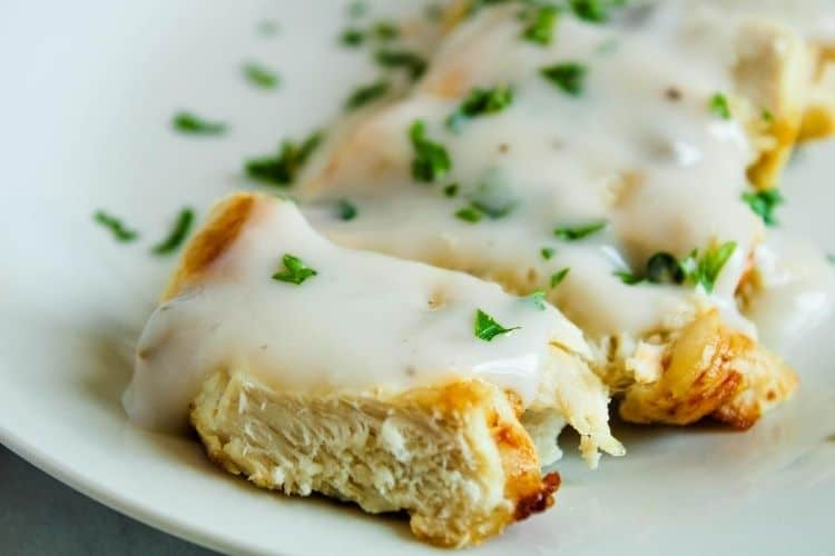 Closeup of sliced air fryer turkey steaks on a white plate with mushroom sauce