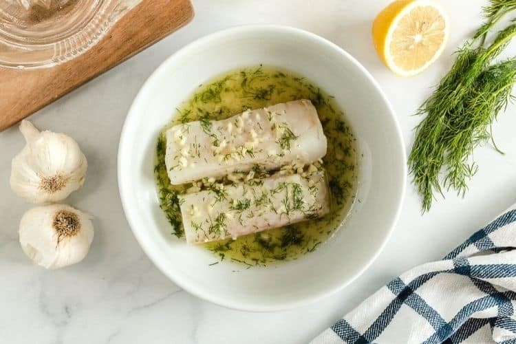 Cod inside a bowl with lemon, garlic, dill, and butter