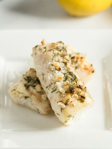 Air Fryer Cod with Lemon and Dill on a white plate with a lemon in the background