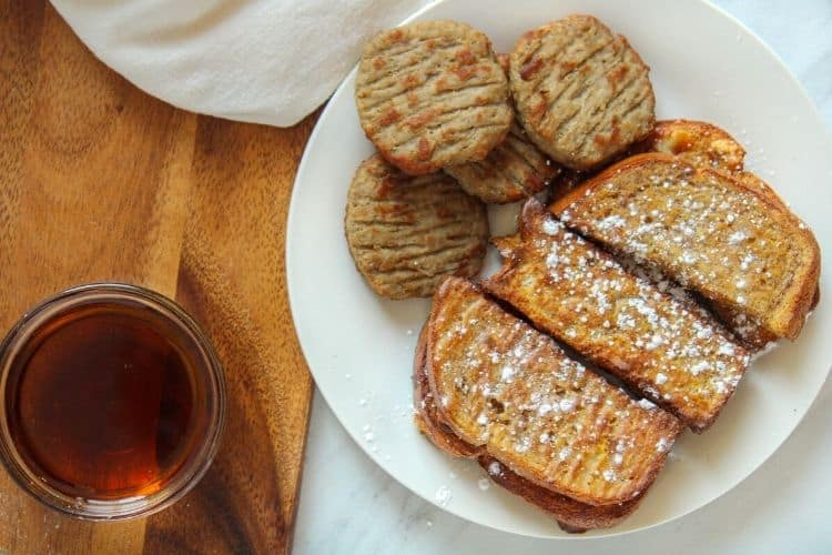 Air Fryer French Toast Sticks and Sausage on a white plate with a bowl of maple syrup to the side