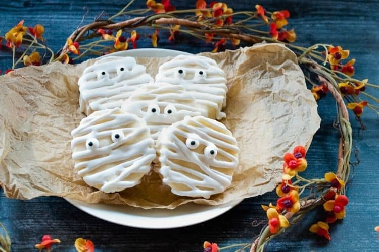 No-Bake Easy Halloween Mummies on a white plate with brown paper surrounded by fall foliage