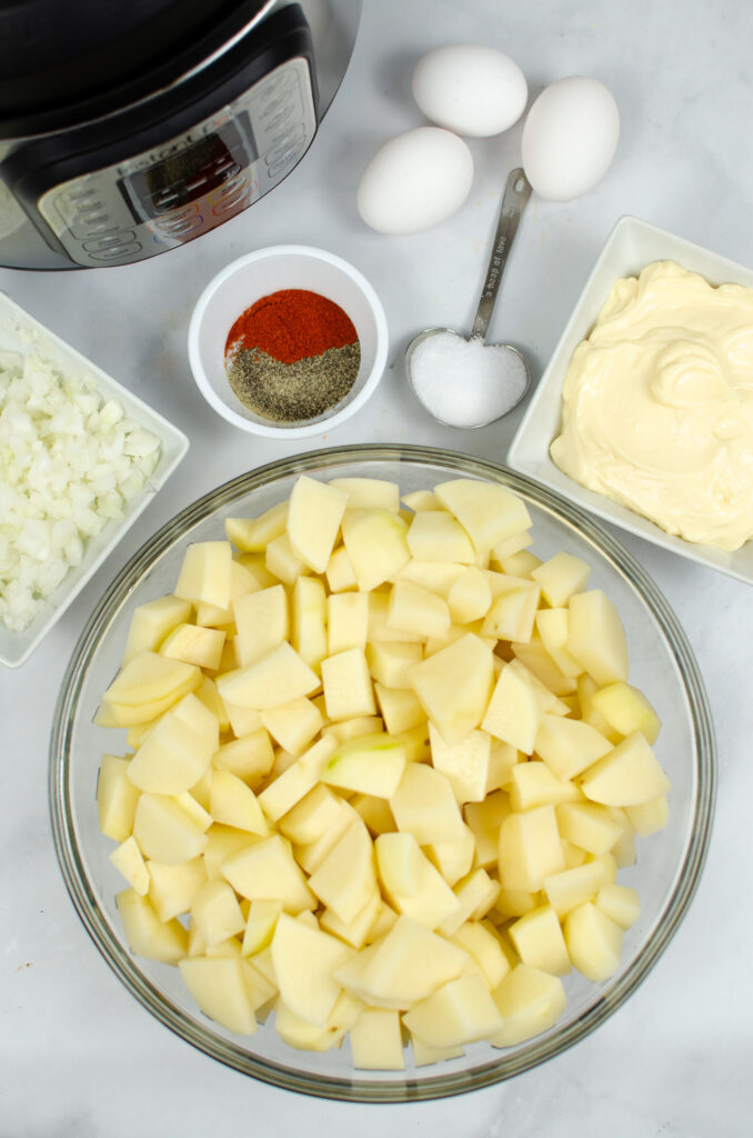 Ingredients for potato salad in bowls and measuring spoons with Instant Pot in the back