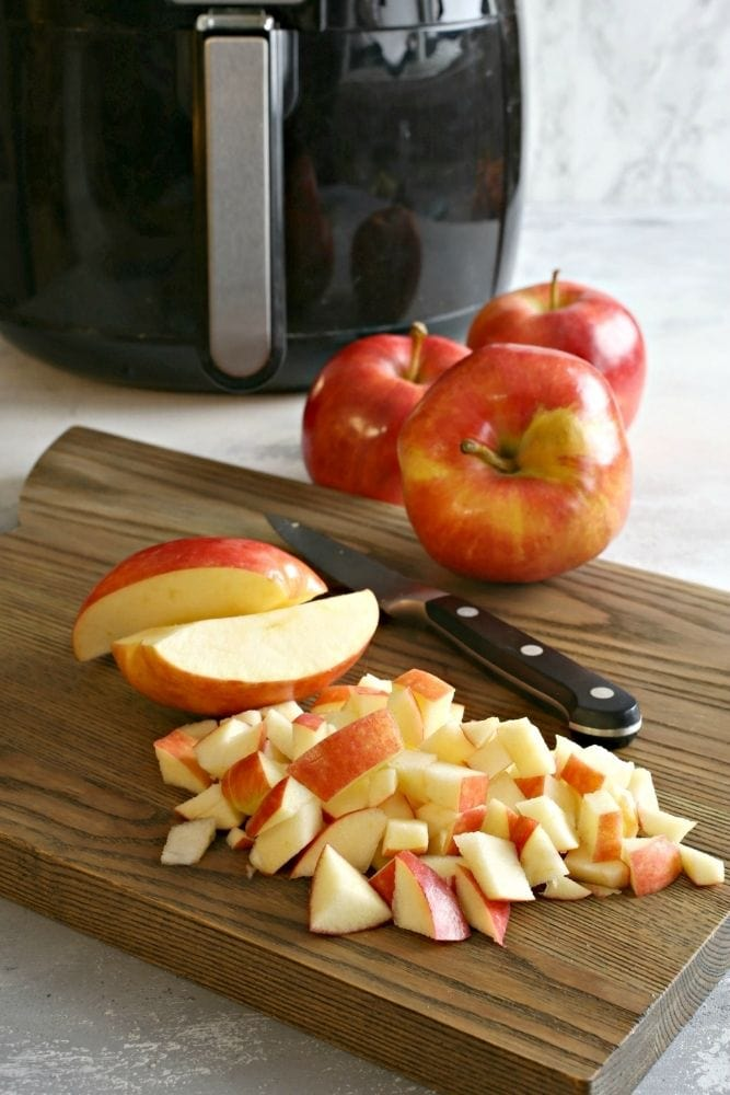 Chopped apples on a cutting board with full apples, a knife, and air fryer in background