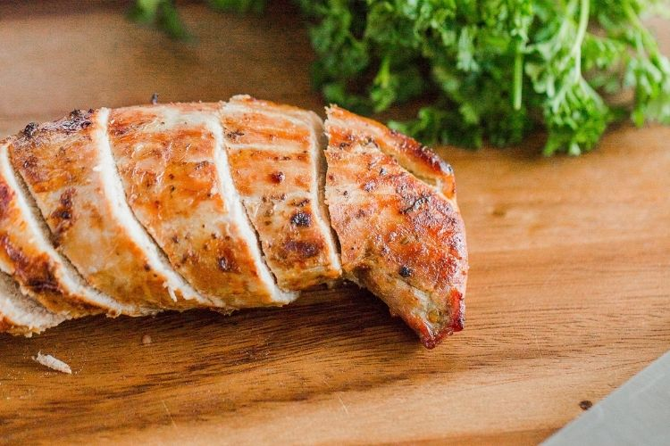 Closeup of sliced air fried pork tenderloin on a cutting board