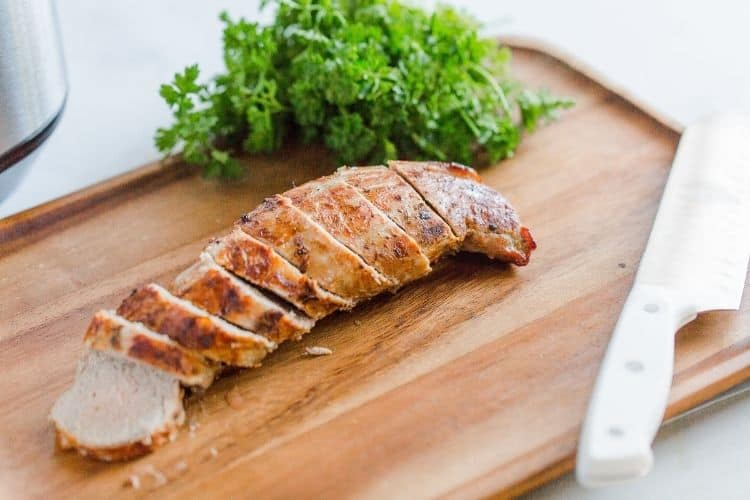 Sliced air fryer pork tenderloin on a cutting board
