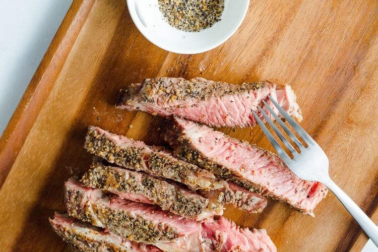 Sliced air fryer steak on a cutting board with fork and bowl of seasoning