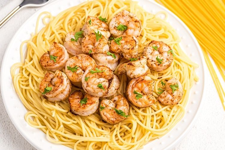 AIr Fryer Shrimp on top of pasta on a white plate from overhead