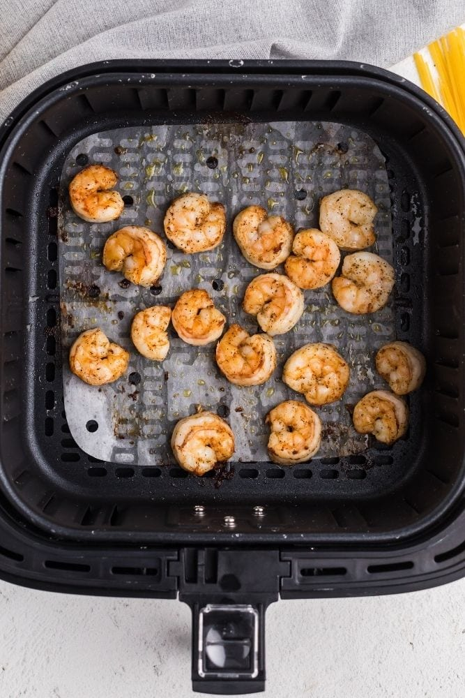 Cooked shrimp in air fryer with parchment paper