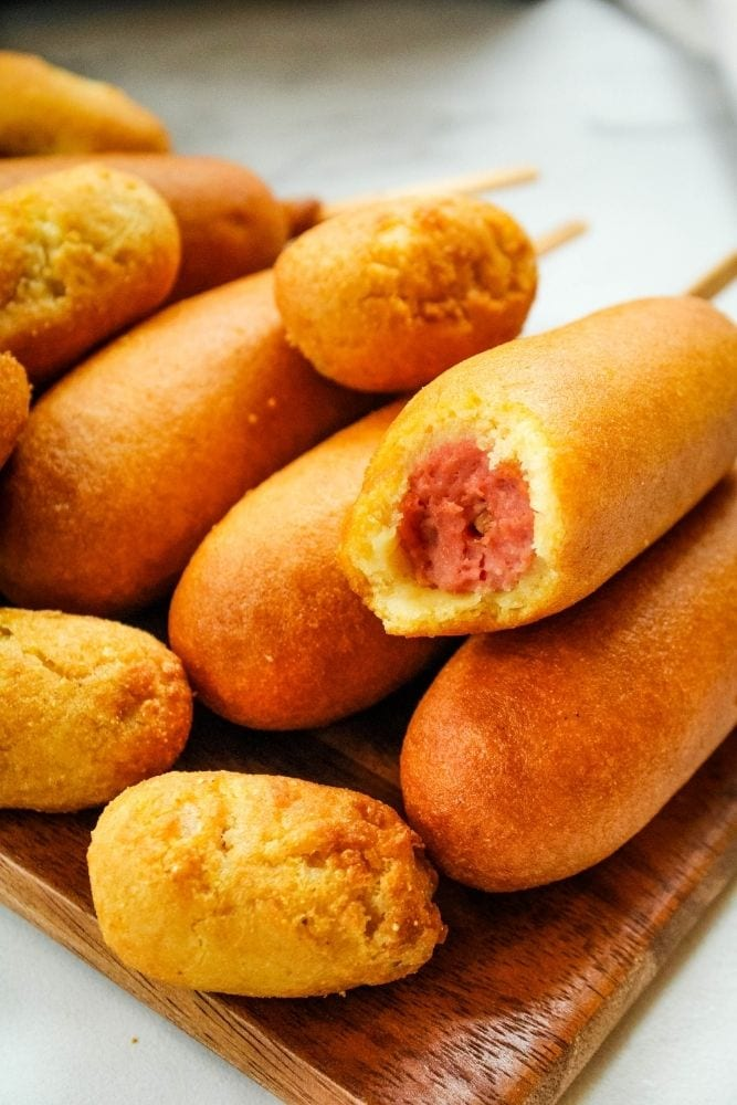 Corn Dogs and Mini Corn Dogs on a brown platter with once corn dog bitten into