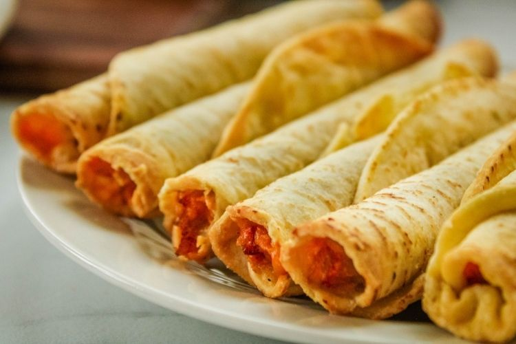 Air Fryer Taquitos in a line on a white plate