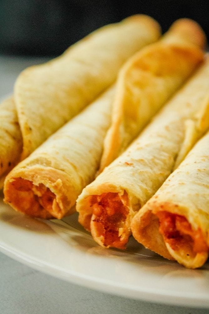 Closeup of air fryer taquitos in a portrait style image on a white plate