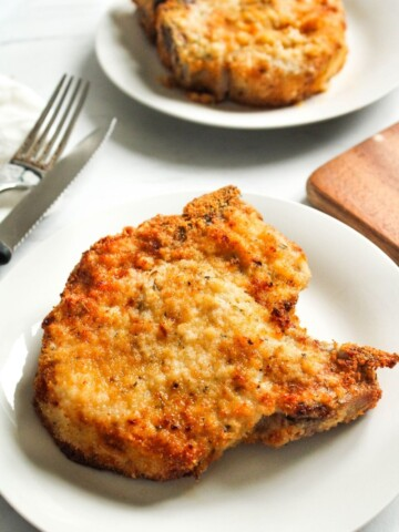 Air Fryer Bone-in Pork Chops on a white plate with fork and knife to the side