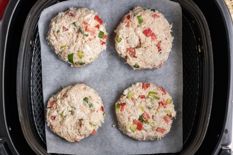 Raw crab cake patties inside the air fryer