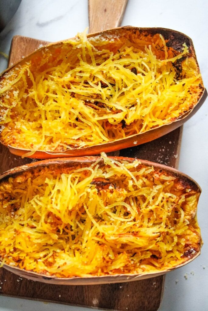 Cooked air fryer spaghetti squash halves cut open with strands pulled