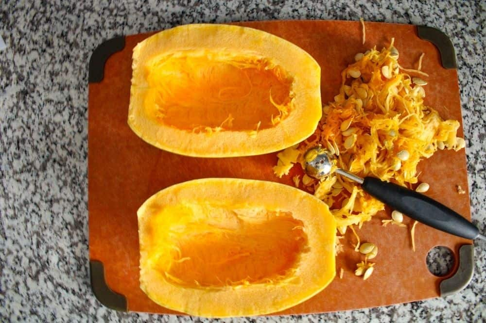 Spaghetti Squash cut in half on a cutting board with seeds cut out and melon baller to the side