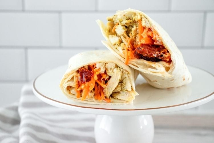 Pesto Chicken Wrap sliced in half on a white plate