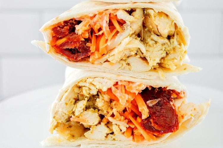 Closeup of chicken wrap sliced in half and stacked on top of each other