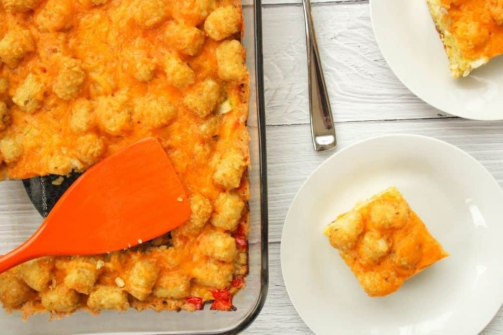 Breakfast Tater Tot Casserole without soup in a 13x9 pan and slices cut out on white plates