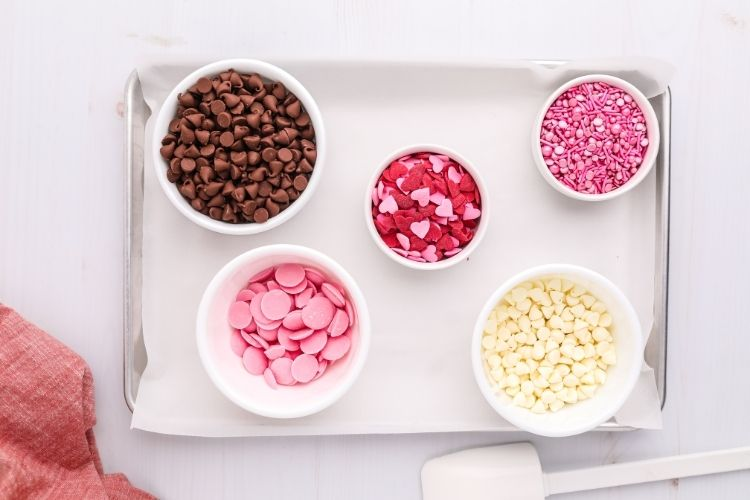 Ingredients for Valentines Day Chocolate Bark on bowls on a cookie tray with parchment paper