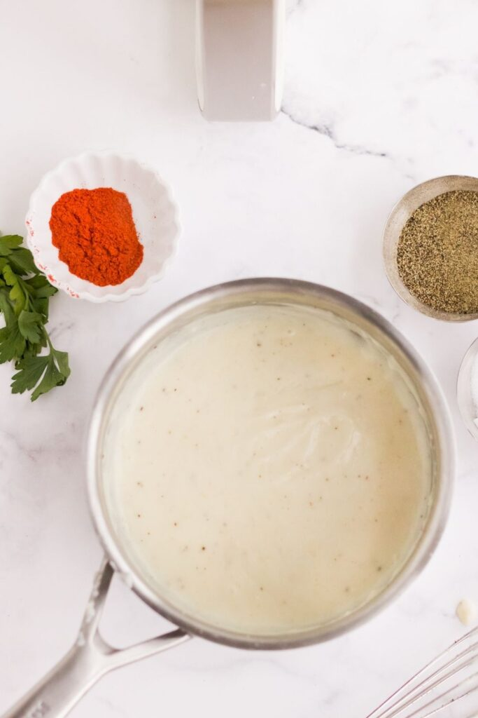 Cooked gravy in a stainless steel pot with ingredients next to it