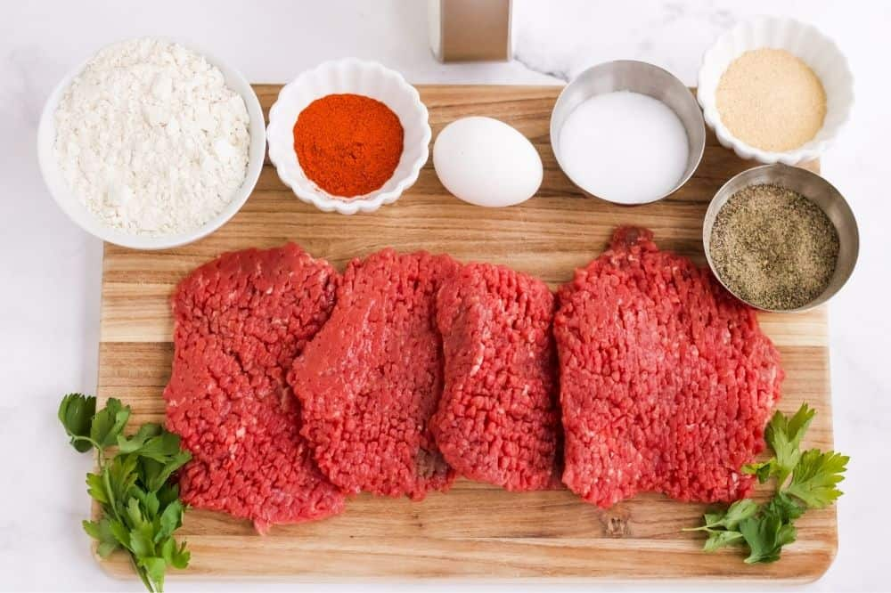Picture of ingredients in bowls and raw cube steak on a cutting board