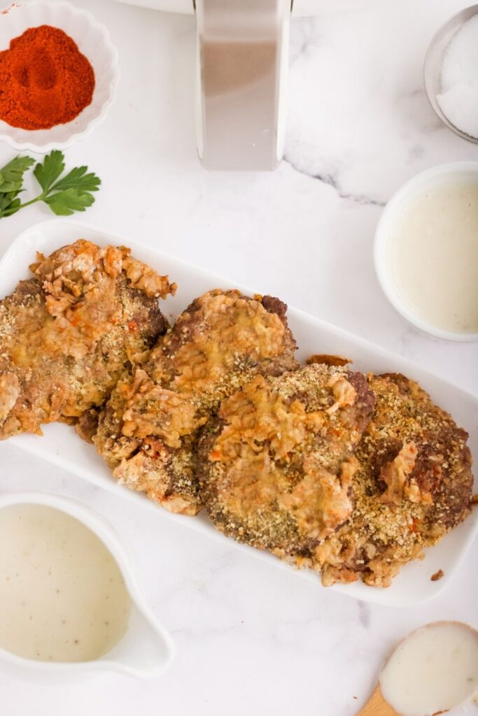 Country Fried Steak served on a long white platter plate with ingredients and air fryer around it