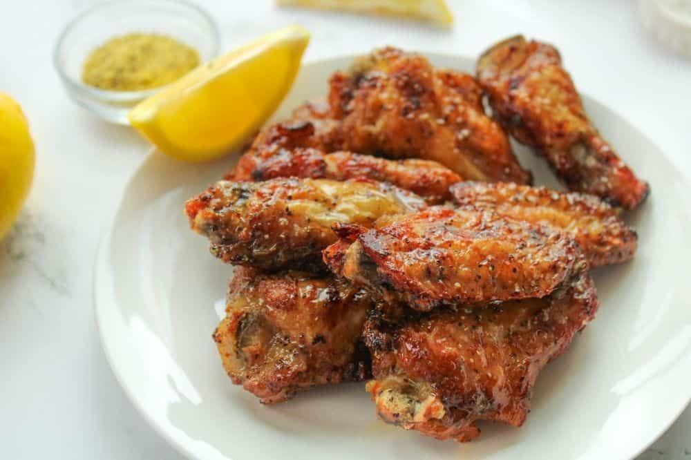 Lemon Pepper Chicken Wings on a white plate with lemon slice and lemon pepper seasoning in background