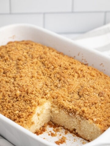 Baked coffee cake in 13x9 white pan with a slice taken out