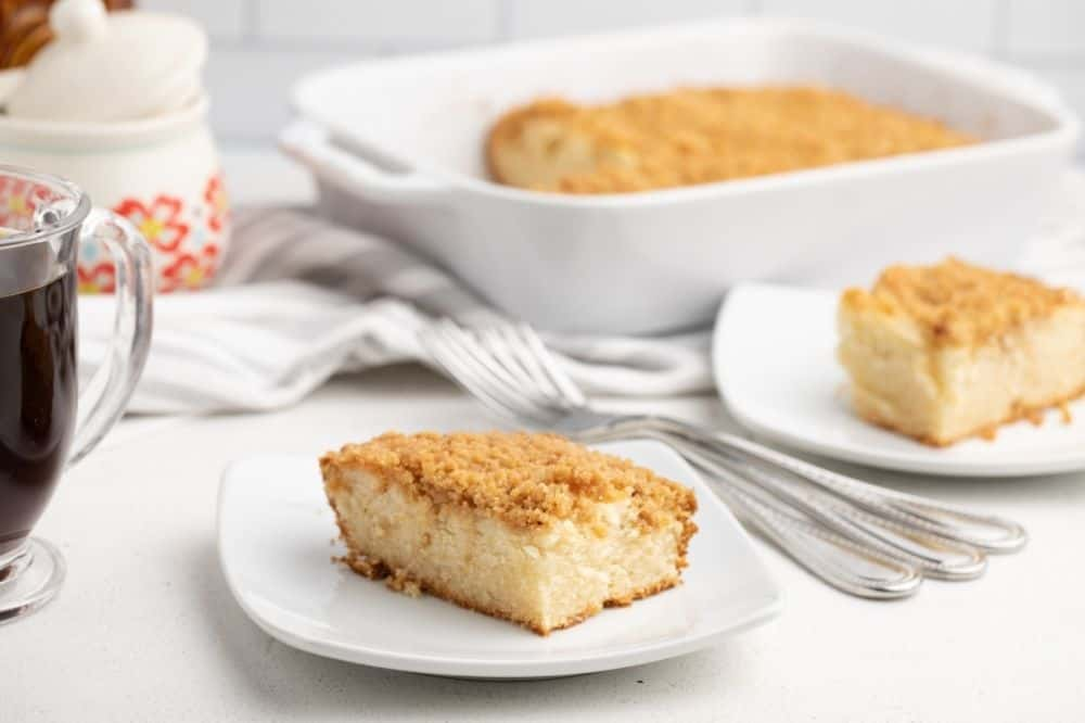 Bisquick Coffee Cake slices on white plate with forks and a 13x9 pan in background