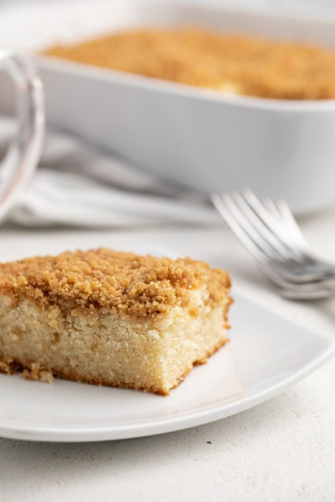 Bisquick Coffee Cake slice on a white plate with forks and pan in the background
