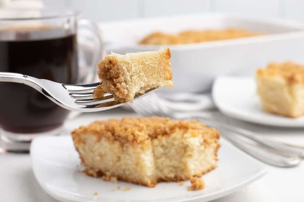 Bisquick Coffee Cake recipe on a white plate with bite-sized piece on fork above the slice