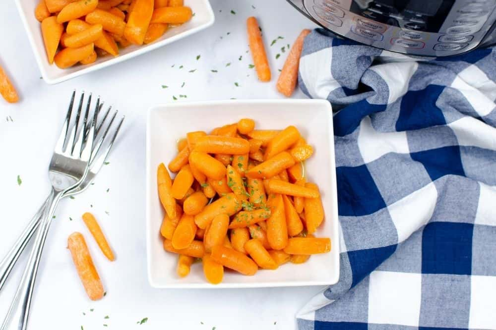 Instant Pot Carrots in a white square bowl with forks and a white and blue checkered tablecloth next to it