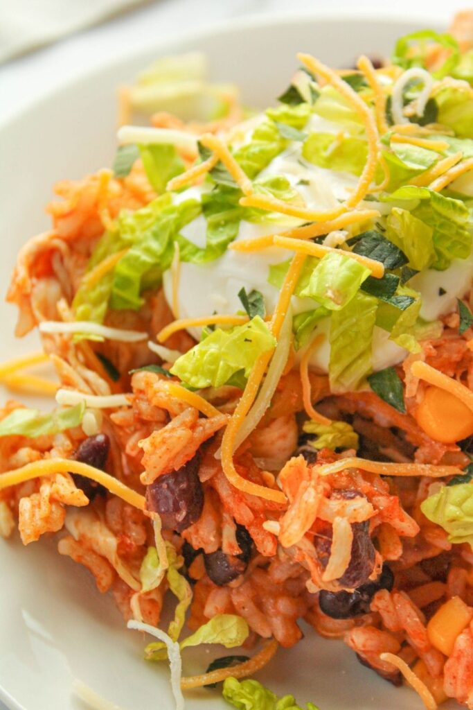 Instant Pot Chicken Taco Bowls topped with sour cream, shredded lettuce, and shredded cheese