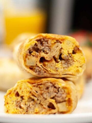 Closeup of air fryer breakfast burrito cut in half stacked on top of each other