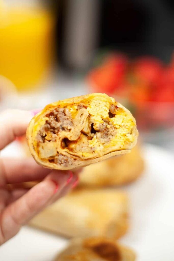 Hand holding half of the cooked breakfast burrito