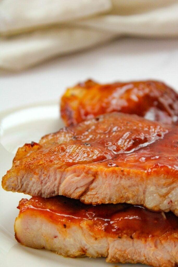 Air Fryer Pork Butt Steaks with BBQ sauce on a white plate cut open