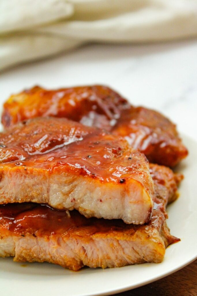 BBQ Air Fryer Pork Steaks on a white plate cut in half stacked on top of each other