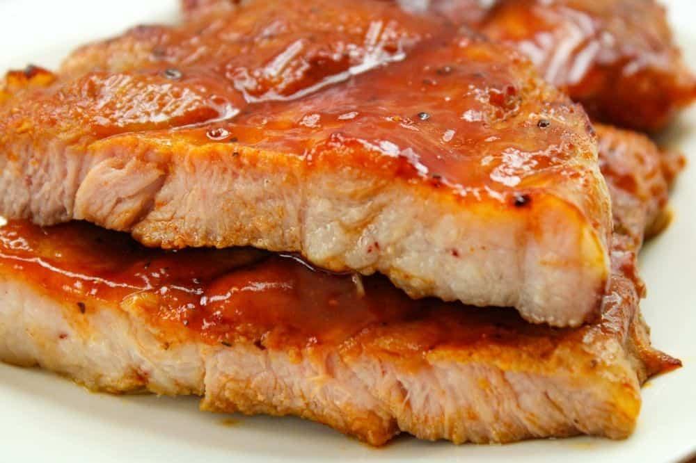 Closeup of air fryer pork steaks on a white plate cut open
