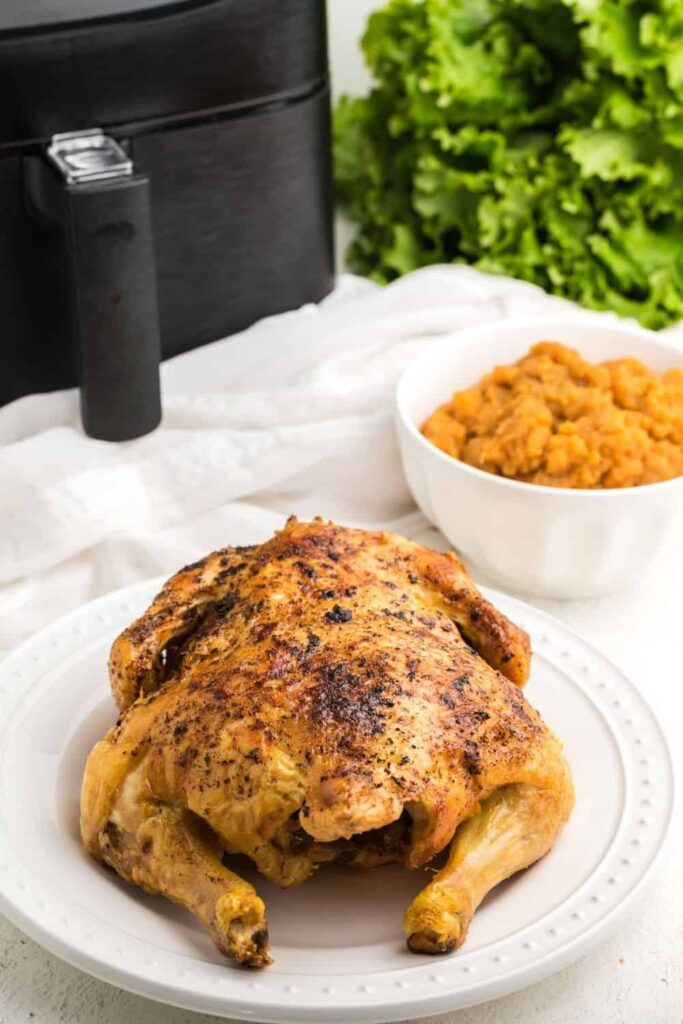 Full cooked whole chicken on a white seving plate with mashed sweet potatoes in a whie bowl, air fryer, and head of lettuce behind it