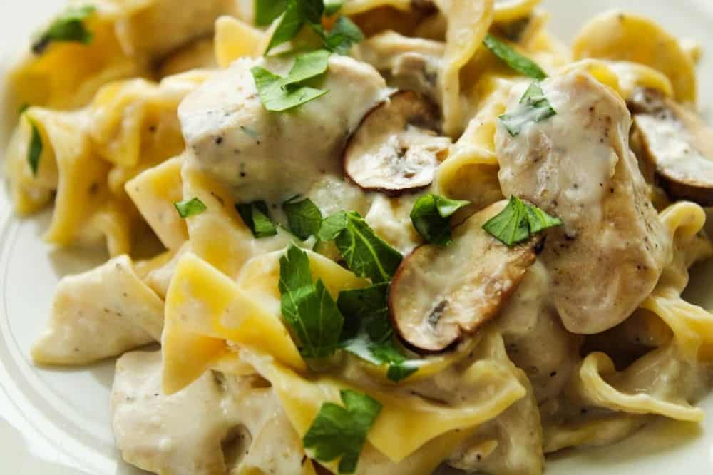 Closeup of chicken stroganoff on a white plate with fresh mushrooms and parsley on top