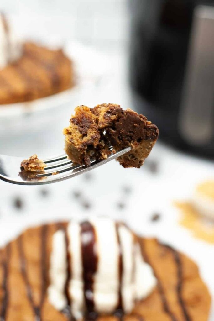 Closeup of a piece of cookie cake on a fork with full cookie cake in background