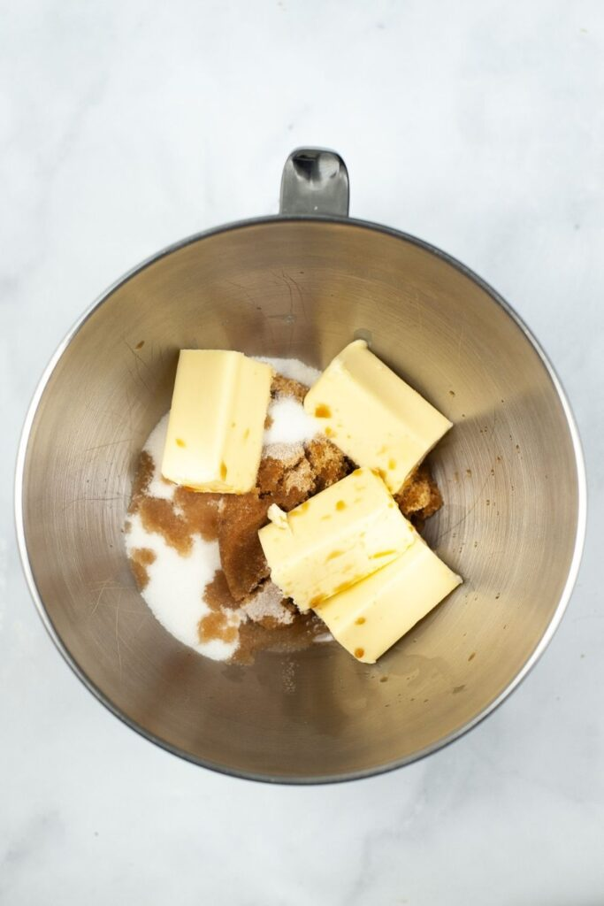 Sugars and butter inside a stainless steel mixing bowl unmixed